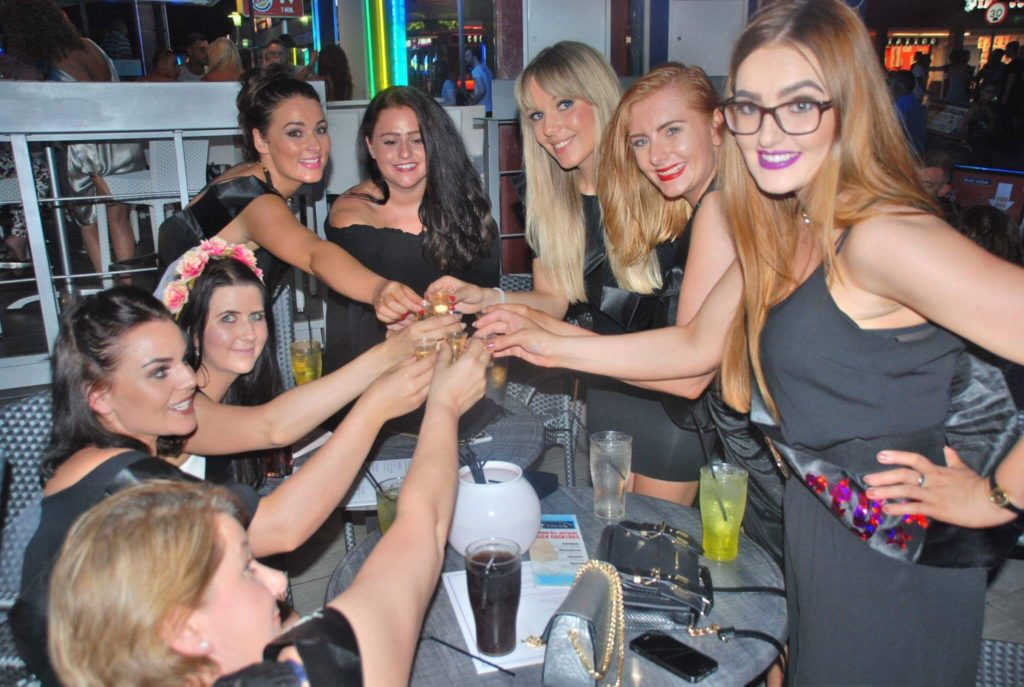 group of girls on a hen party doing cheers in a bar in magaluf